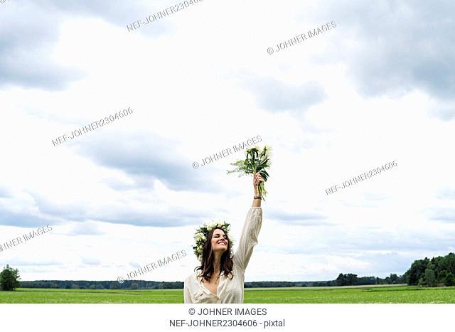 Woman wearing wreath standing in field