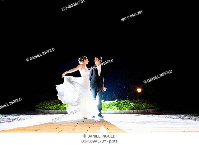 Romantic newlywed mid adult couple dancing in garden at night