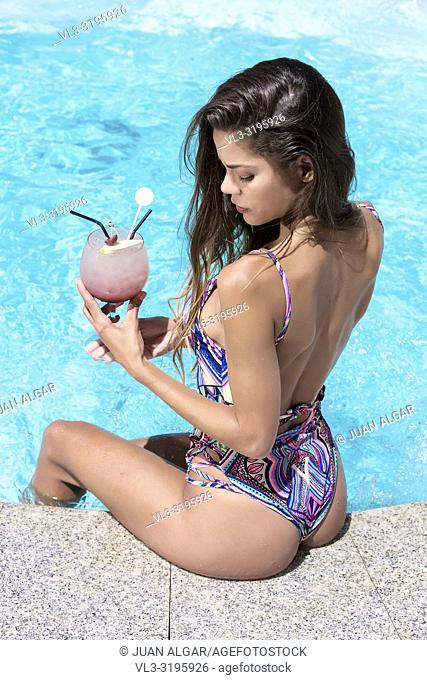 Back view of attractive female in colorful swimsuit sitting on spa pool edge and holding glass with cocktail