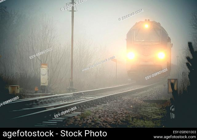 Cargo train locomotive emerging from the mist when approaching to the railway junction, monochrome image
