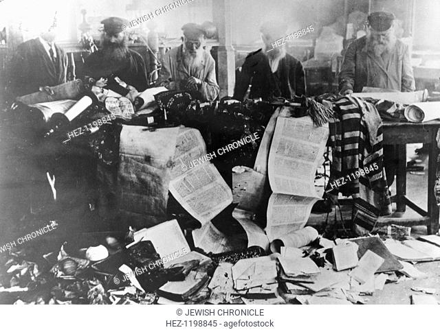Torah scrolls desecrated during the pogroms, Russia, 1881. Jewish men survey damage done to sacred religious texts