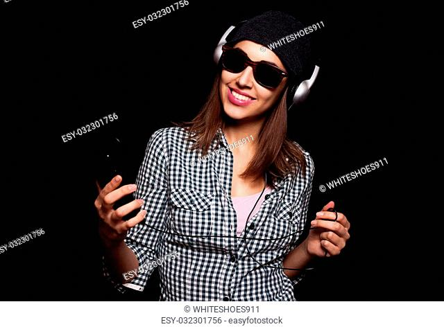 beautiful girl happy listening to music with big headphones with a phone or player, knit cap, photo studio, portrait of a woman on black background