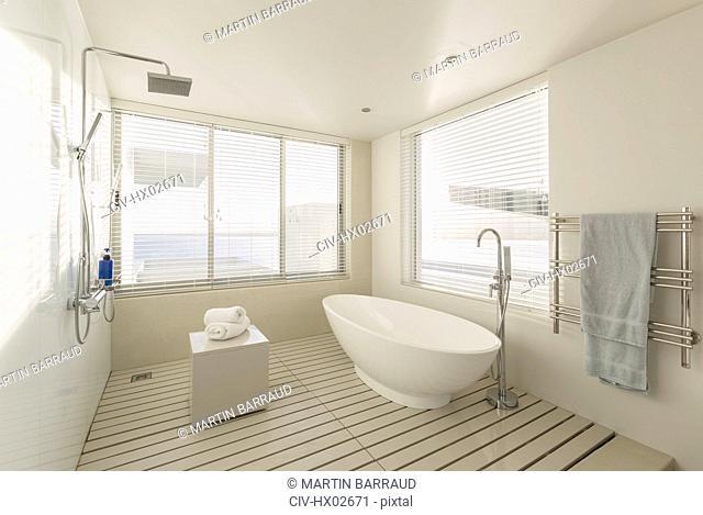Minimalist, modern luxury home showcase bathroom with soaking tub and shower