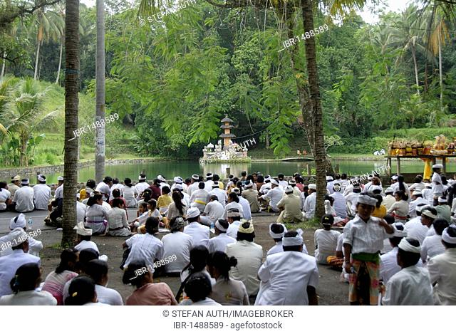 Bali Hinduism, many religious believers meeting in ceremony, sitting on the floor, Pura Taman Mumbul Temple with lake, near Ubud, Bali, Indonesia