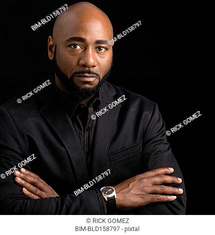 Frowning black businessman with arms crossed