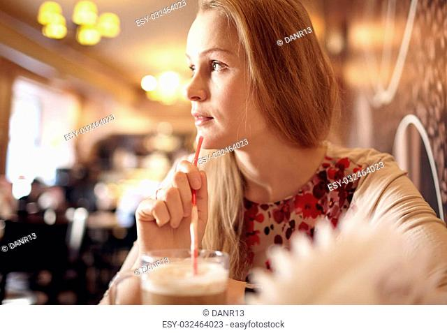 Portrait of girl enjoying coffee in cafe and looking through the window. Beautiful vintage interior in blur with natural sunlight