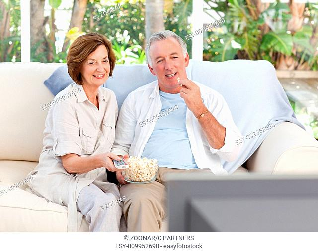 Seniors watching tv at home