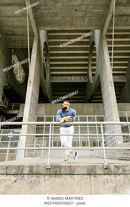 Bearded hipster businessman with smartphone leaning on railing and looking at distance