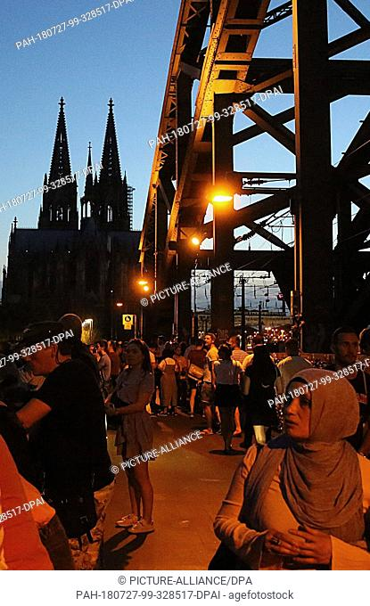 27 July 2018, Germany, Cologne: Onlookers are waiting for the lunar eclipse on the Hohenzollern Bridge. During the longest lunar eclipse of the 21st century