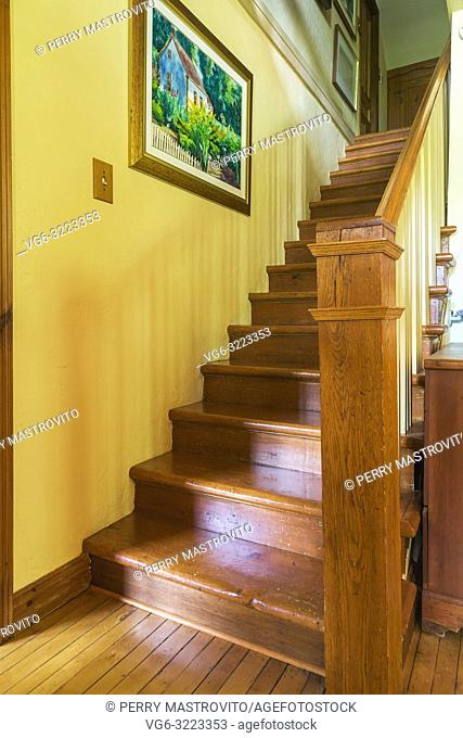 Pinewood stairs leading to the upper floor inside an old circa 1850 Canadiana cottage style home