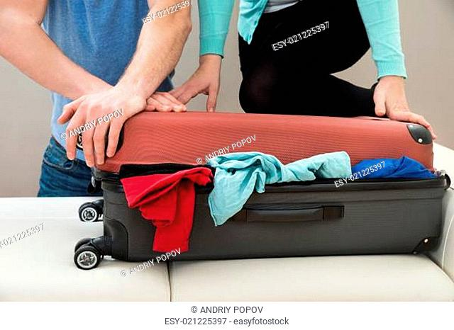 Close-up Of Couple Together Packing Luggage At Home