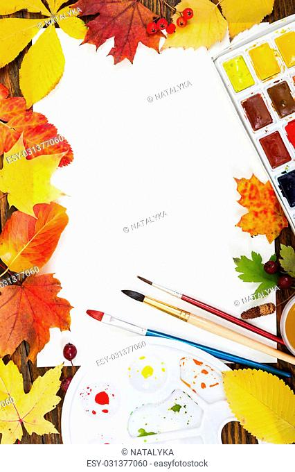 Workplace of artist. Sheet of paper, paints, palette, brushes and autumn leaves. Autumn concept. Top view