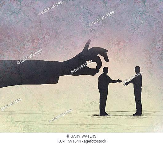 Large hand flicking small businessman shaking hands