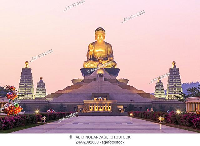 Kaohsiung, Taiwan: Sunset at Fo Guang Shan, the biggest buddist temple of Kaohsiung in Taiwan, with a buddhist monk walking by