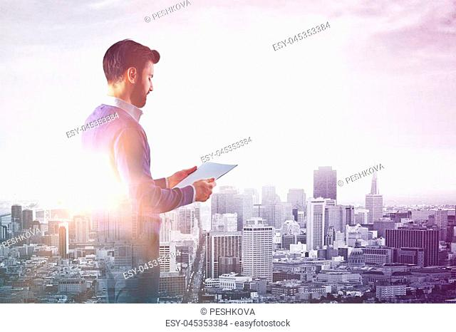 Side view of young businessman examining document on abstract city background with copy space. Occupation concept. Double exposure