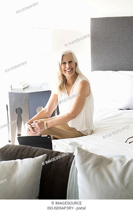 Portrait of senior woman sitting on bed, smiling