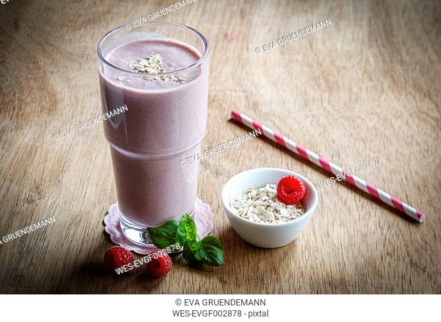 Glass of raspberry milkshake with oatflakes and basil