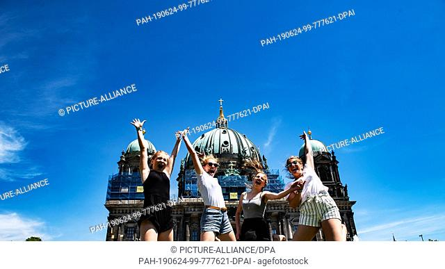 24 June 2019, Berlin: Lena (l-r), Mette, Josefine and Sophia from Lübeck jump into the air in front of the Berlin Cathedral