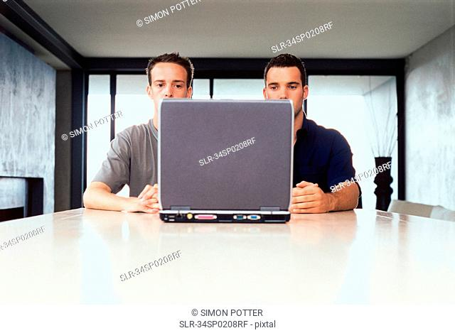 Businessmen using laptop together