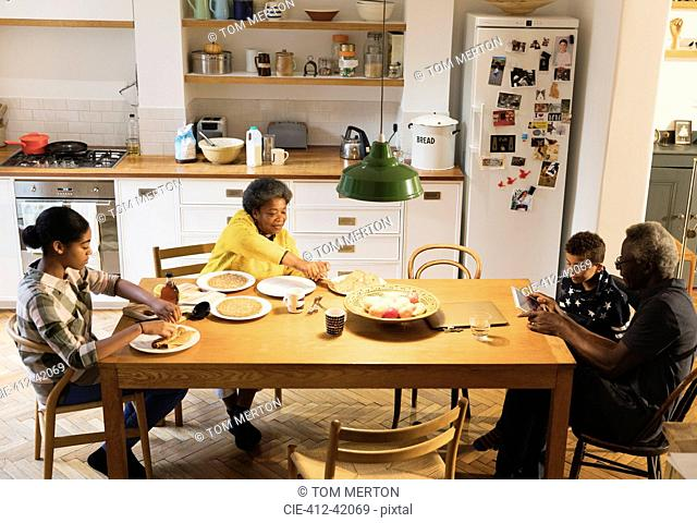 Grandparents and grandchildren eating and using digital tablet at dining table