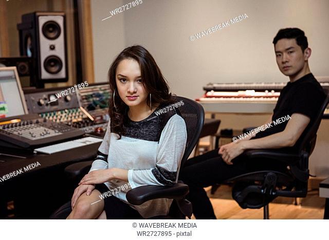 Audio engineers sitting in recording studio