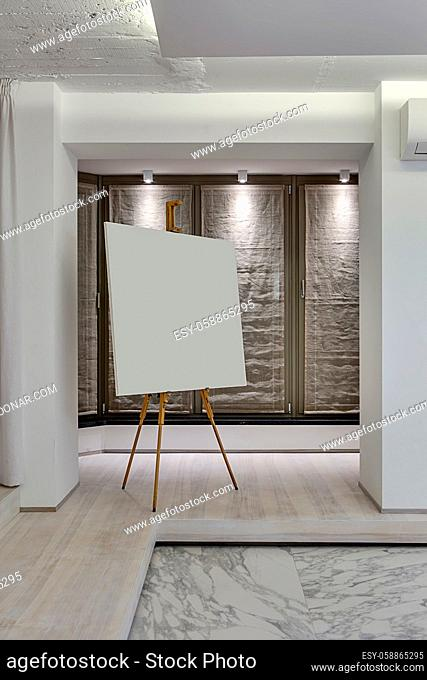 Room in a modern style with white walls, parquet and light tiles with patterns on the floor. There is a canvas on the wooden easel, tall windows with curtains