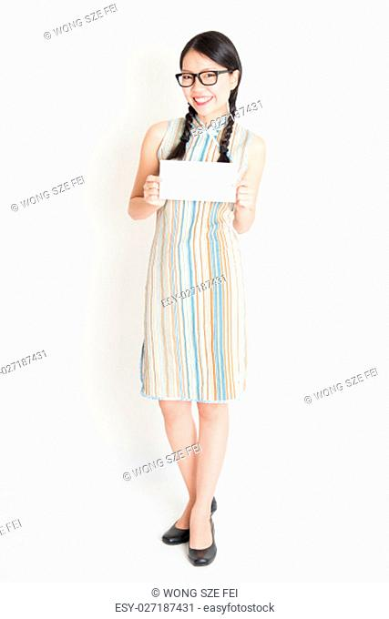 Portrait of young Asian female in traditional qipao dress hand holding white blank paper card, celebrating Chinese Lunar New Year or spring festival