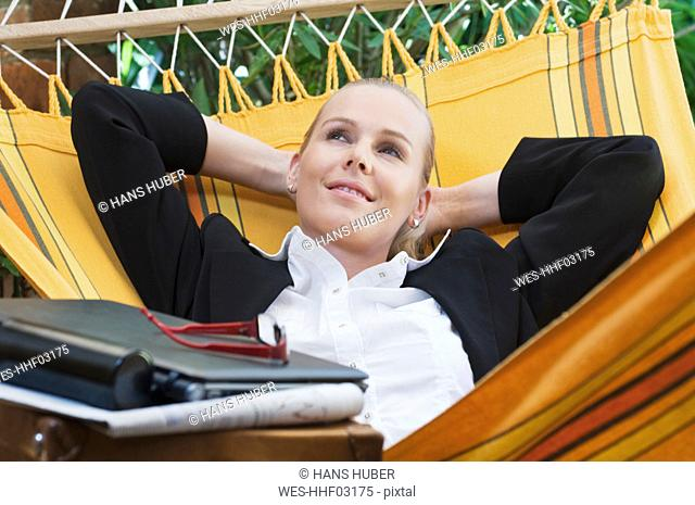 Austria, Businesswoman lying in hammock, smiling