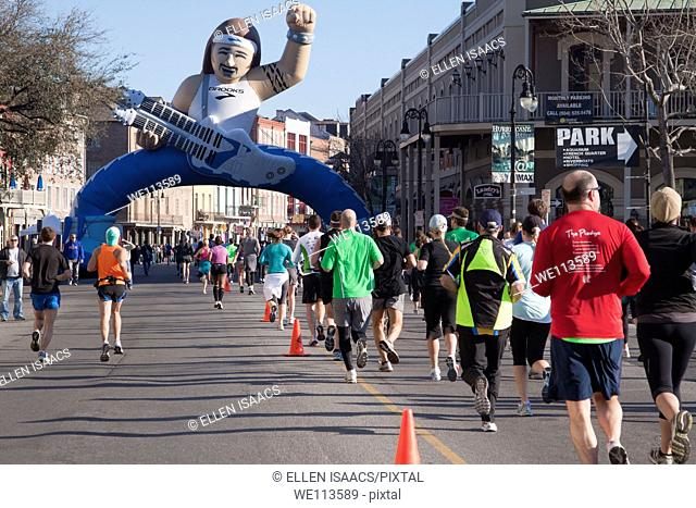 Crowd of racers running toward the giant inflated guitar player on Decatur Street in the Rock and Roll Marathon in New Orleans