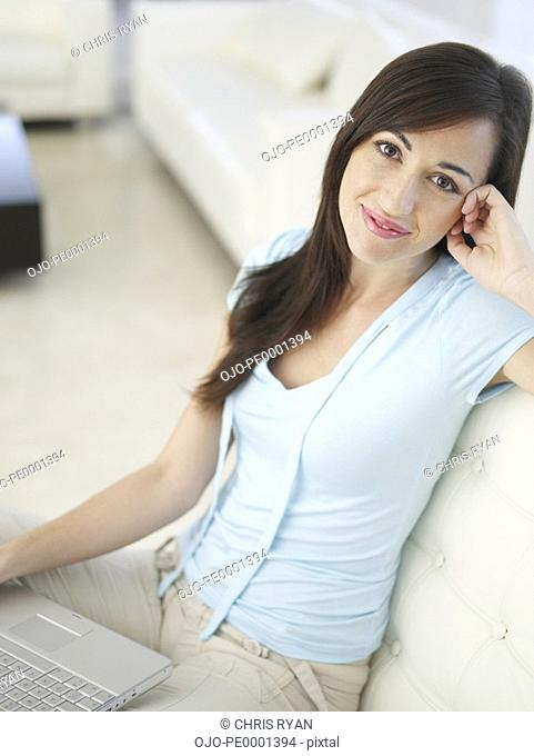 Woman sitting with laptop smiling