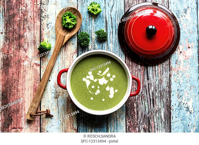 Broccoli soup, broccoli florets and a cooking spoon