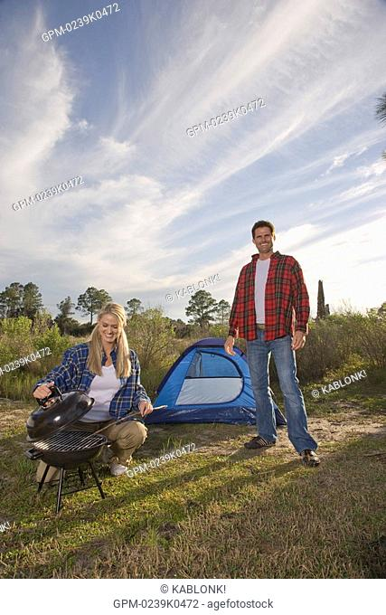 Couple by tent, woman preparing food on barbecue at campsite