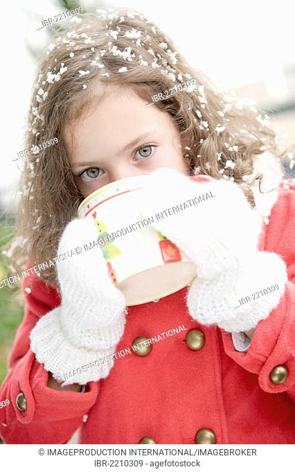 Girl with snowflakes in her hair drinking from a cup