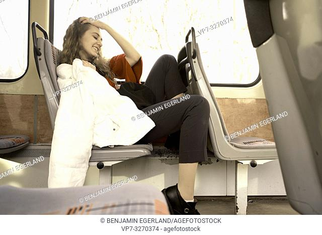 young woman sitting in public transport, in city Cottbus, Brandenburg, Germany
