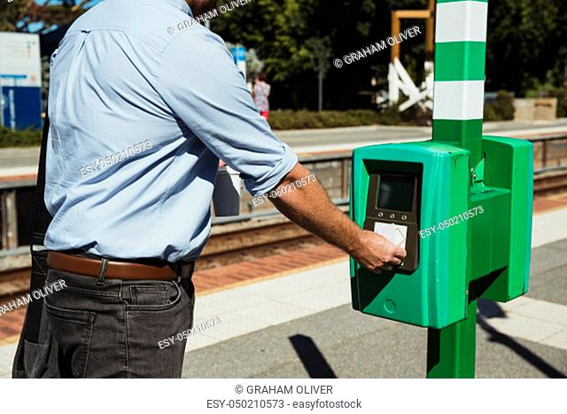 A rear-view shot of an unrecognizable mid-adult businessman buying a train ticket to begin his commute to work