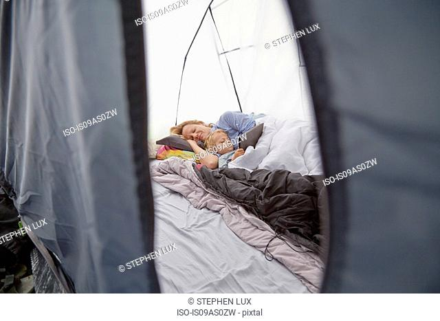 Mother lying in tent with toddler son using digital tablet
