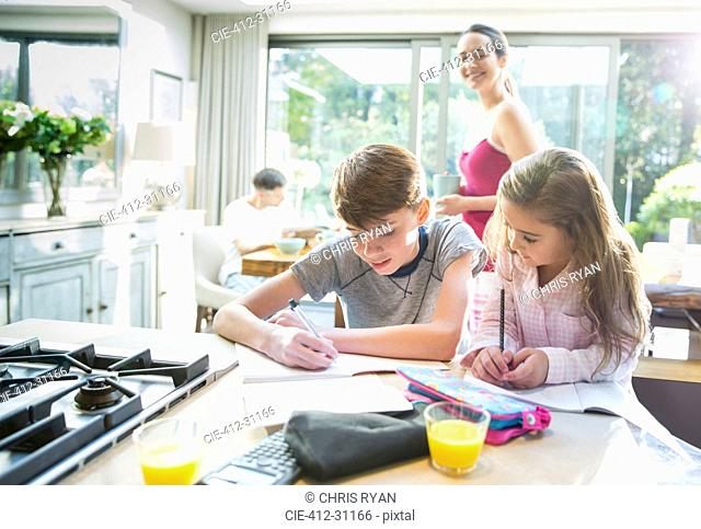 Mother watching brother and sister doing homework at kitchen counter