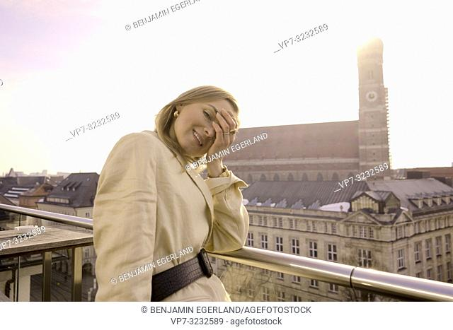 tourist blogger woman on balcony next to church Frauenkirche, Marienkirche, in Munich, Bavaria, Germany