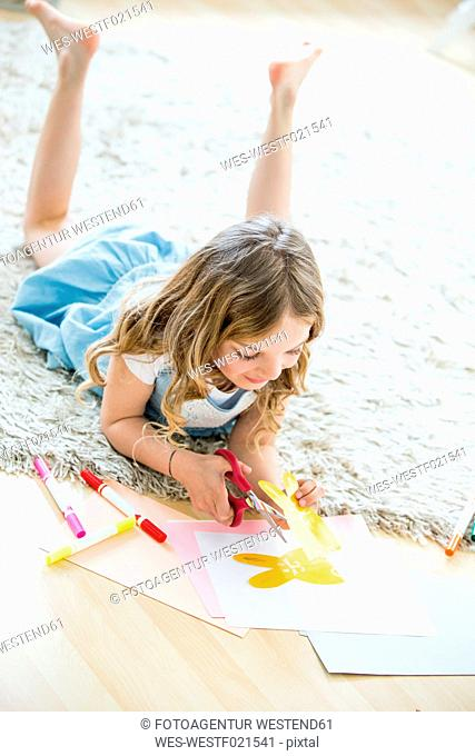 Little girl cutting out paper Easter bunnies