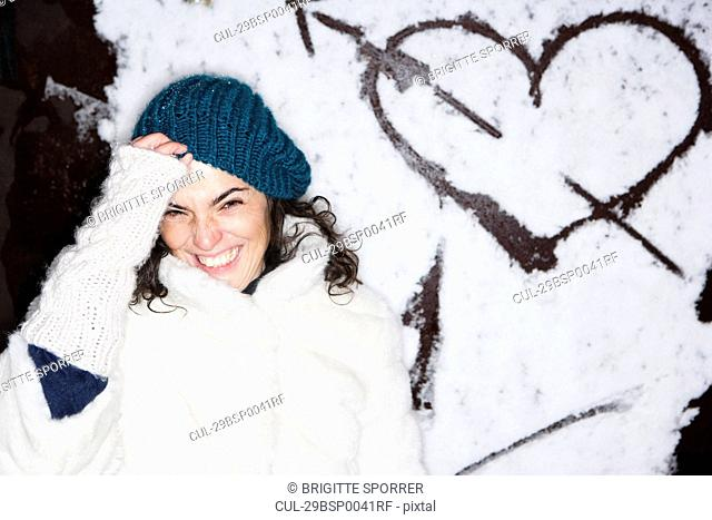Laughing woman in front of painted heart
