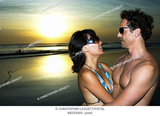 young couple embracing on the beach with sunset in the background