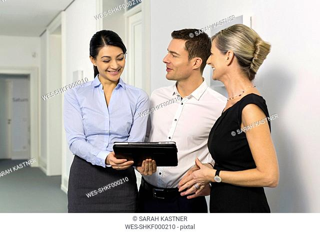 Businesspeople with digital tablet on office floor