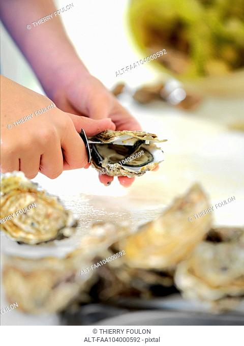 Woman shucking oyster