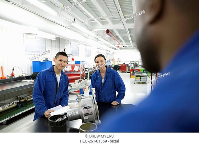 Smiling helicopter mechanics talking in workshop