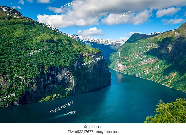 Cruising ship is going to North Sea by narrow fjord water channel, surrounded by steep mountains. Aerial photo of Geiranger fjord, Norway