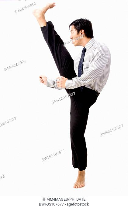 A young asian businessman in corporate dress does a high karate kick
