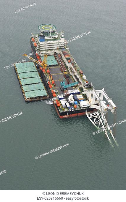 The cargo ship with the crane, the top view. Pipelaying barge