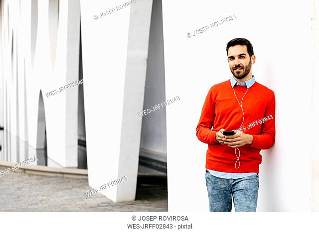 Casual businessman leaning on wall, using earphones and smartphone