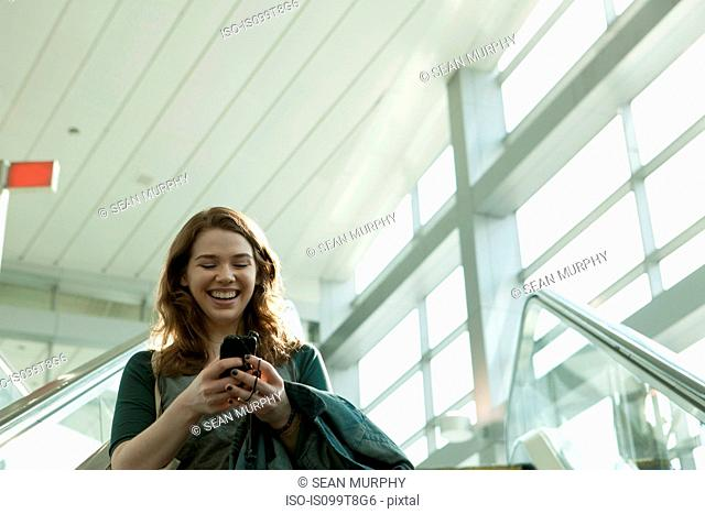 Young woman on escalator using smartphone