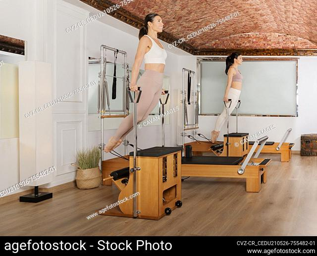 two girls exercising arms on the pilates combo chair